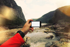 First-person view, the man takes a photo of a mountain river on smartfon. Concept, white screen smartphone. POV view Stock Photo