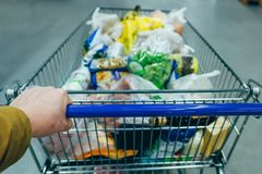 First person view. man with trolley in grocery store. shopping c. Oncept stock image