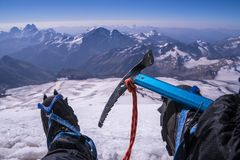 First person view to body and far landscape. Man legs in crampons with an ice axe take a rest on the top of mountain royalty free stock image