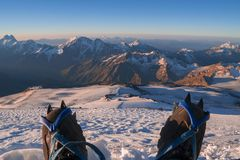 First person view to body and far landscape. Man legs in crampons take a rest on the top of mountain. Feet in trekking. Boots on the background of the snowy Stock Photo