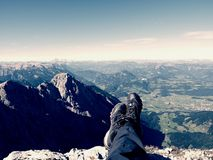 First person view to body and far landscape. Man legs take a rest on the top of mountain. stock images
