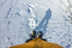 First person view to legs in crampons standing in the snow.  royalty free stock photos