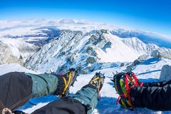 First person view to legs in crampons take a rest on the top of mountain.  Stock Photos