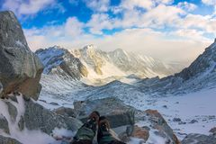 First person view to legs in crampons take a rest on the top of mountain.  Royalty Free Stock Photos