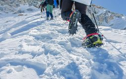 First person view to legs in crampons take a rest on the top of mountain.  Stock Images