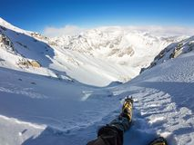First person view to legs in crampons take a rest on the top of mountain.  Royalty Free Stock Photography