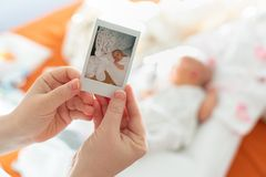 The first photo of a newborn in the hands of a female mother against a child stock photography
