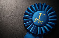 First place award. Rosette over dark background with copy space Royalty Free Stock Image