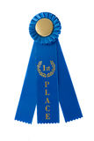A first place blue ribbon isolated on white. A blue ribbon that says first place is isolated on a white background stock photo