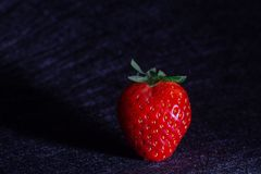 STRAWBERRY PROJECTING ITS SHADOW ISOLATED IN BACKGROUND WITH BLACK TEXTURES royalty free stock images