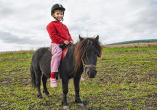 First pony-ride. Sweet little girl filled with joy on her first pony ride Royalty Free Stock Photography