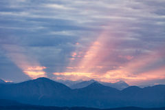First rays rising sun over dark blue morning Alps mountains Royalty Free Stock Photo