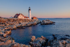 The first rays of sunrise hits the Maine Coast turning the Rocks. And buildings at the Portland Head Lighthouse orange Royalty Free Stock Image