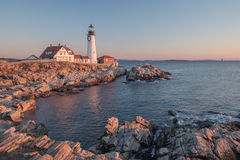 The first rays of sunrise hits the Maine Coast turning the Rocks. And buildings at the Portland Head Lighthouse orange Stock Images