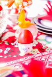 First red egg, in focuse, for Eastern in Serbia. With decoration on table Stock Image