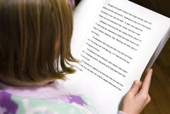 First Research Paper. A young 2nd grade student reviews her research paper before presenting it the next day at school Royalty Free Stock Photography