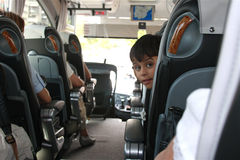 First Ride Alone. Young boy on first trip on a bus looking back from seat Stock Photos