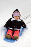 First ride in the snow 1. A toddler girl bewildered by her first ride in a snow on a sleigh/sledge Royalty Free Stock Photography