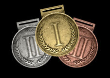 First Second And Third Medals. A closeup set of gold, silver and bronze medals on a dark background Royalty Free Stock Images