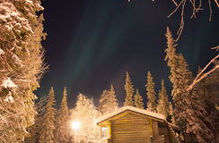 The first signs of Northern Lights above the pine trees and cabin Stock Photography