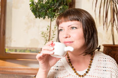 First sip. Portrait of a young woman drinking her morning coffee over a breakfast in the kitchen Royalty Free Stock Photography