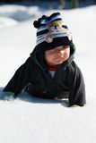 First snow. Little baby boy laying on the snow feeling unsure Stock Photos
