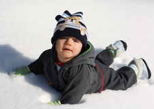First snow. Little baby boy laying on the snow during sunny day Stock Photos
