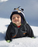 First snow. Little baby boy laying on the snow during sunny day Royalty Free Stock Photo