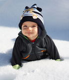 First snow. Little baby boy laying on the snow during sunny day Stock Images