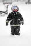 First Snow. Cute boy in a snowstorm Royalty Free Stock Photography