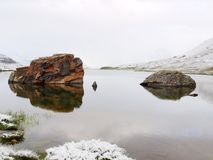 First snow at Alpine lake. Autumn lake in Alps with mirror level and snowy grass and boulders around. Misty sharp peaks Royalty Free Stock Photo