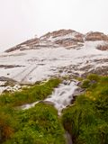 First snow in Alps touristic region. Fresh green meadow with rapids stream. Peaks of Alps mountains in background. Stock Image
