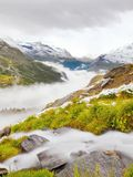 First snow in Alps touristic region. Fresh green meadow with rapids stream. Peaks of Alps mountains in background. Royalty Free Stock Photos