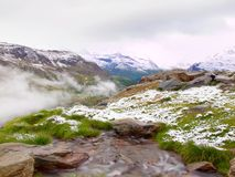 First snow in Alps touristic region. Fresh green meadow with rapids stream. Peaks of Alps mountains in background. Foamy water is running down over slipper royalty free stock images