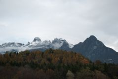 The first snow at altitude. The fantasies and colors of autumn on the beautiful Dolomites royalty free stock image