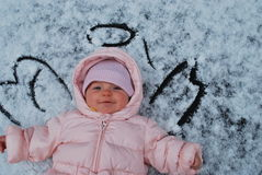 First snow. Baby for the first time on the snow. Happily looking at a snowy sky stock photos