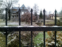 First snow. A Little of snow lies on the grass, trees and fence around the two-story private house Stock Photography