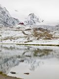 First snow in mountains. Autumn lake in Alps with mirror level. Misty sharp peaks of  high mountains Royalty Free Stock Photo