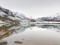 First snow in mountains. Autumn lake in Alps with mirror level. Misty sharp peaks of  high mountains Stock Photo