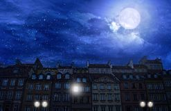 The first snow in the old town of Warsaw. On the background of the full moon stock photo