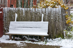 The first snow. Pure white snow evenly lay down on the wooden bench outside a rural home stock images