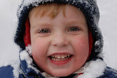 First snow. Snowflakes on the face smiling boy Royalty Free Stock Images