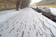 First snow on the street. On the road the traces of shoes Stock Photos