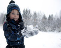 First snowball. Young boy trying to make a snowball Stock Photo