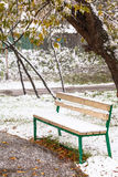 First snowfall and empty bench in city park Stock Images