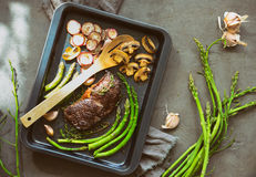First spring garden vegetables and beef roasted. Beef and roasted radishes and asparagus and some mushrooms in a sheet pan lighten up by spring sunshine, high royalty free stock photography