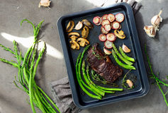 First spring garden vegetables and beef roasted. Beef and roasted radishes and asparagus and some mushrooms in a sheet pan lighten up by spring sunshine, high royalty free stock photo
