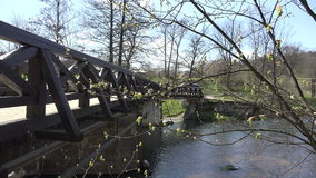 First spring green leaves on tree twig and bridge over river. 4K. First spring green leaves on tree twigs and river water fall flow under wooden bridge. Static stock video footage
