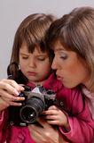 First step. Mother teaching little daughter how to use camera Stock Photo