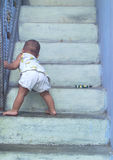 First Step. A Cute Baby Boy walks step by step on the stairs Stock Image